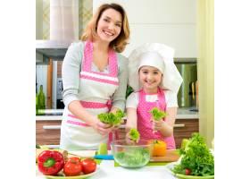 欢快微笑的母女俩在厨房做沙拉_11177201