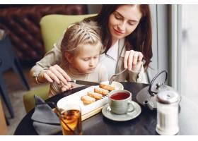 母亲带着女儿坐在咖啡馆里_7724950