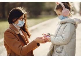 母亲带着女儿戴着口罩走在外面_7710449