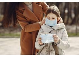 母亲带着女儿戴着口罩走在外面_7710664