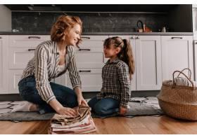 母亲和女儿穿着相似的衣服坐在厨房的地板_12677641