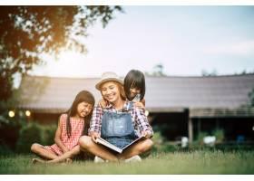 母亲在自家花园给两个小女儿讲故事_2524867