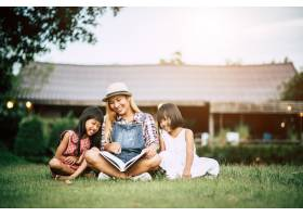 母亲在自家花园给两个小女儿讲故事_2524870