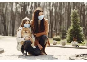 母亲带着女儿戴着口罩走在外面_7727225