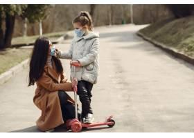 母亲带着女儿戴着口罩走在外面_7727240