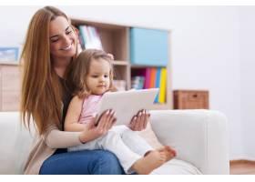 母亲带着孩子在家使用数字平板电脑_10979266