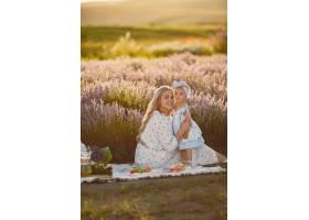 母亲带着年幼的女儿在薰衣草地里美丽的女_10062794