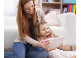 母女俩在使用数字平板电脑的过程中玩得开心_10979328