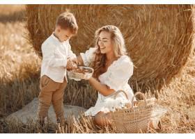 母子俩夏天在黄色的麦田上堆放干草或打_10885050