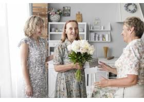 微笑的老妇人手持花束和礼物与女儿和孙女_5043997