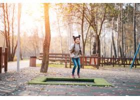 快乐的女学生在公园的小蹦床上跳_7560343