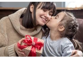 快乐的年轻妈妈和她可爱的女儿在一起祝贺_12339230