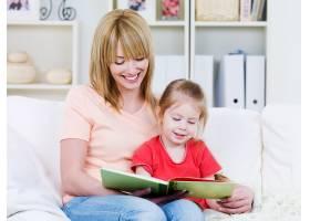 快乐的年轻母亲和她微笑的小女儿一起在室内_10879576