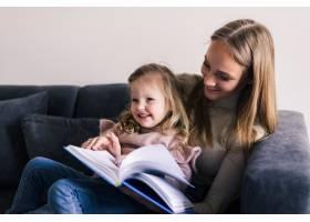 快乐的母女俩坐在客厅舒适的沙发上看书_8471569