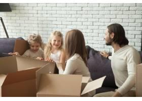快乐的父母带着孩子在起居室里玩拆包游戏_3938136