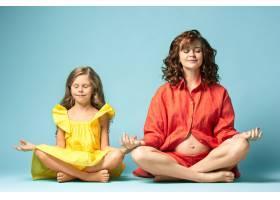 怀孕的母亲和十几岁的女儿蓝色背景上的家_9060048