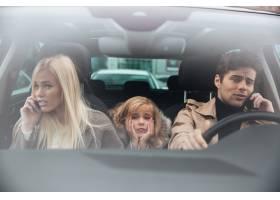 悲伤的小女孩坐在车里而她的父母在聊天_6873790