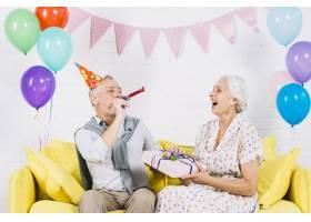 拿着生日礼物看着丈夫吹响派对号角的快乐女_3492389