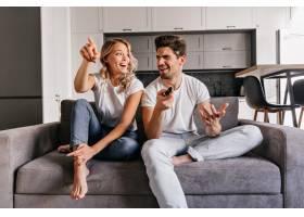 感兴趣的金发女郎看电视坐在舒适沙发上微_12152287