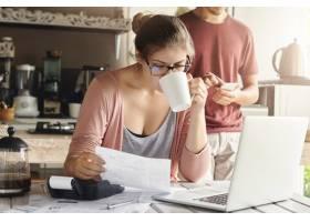 戴着眼镜的迷人的严肃女性喝着咖啡手里拿_9532802