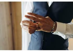 新郎拿着结婚戒指站在旅馆的窗前_3984966