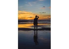 日落时海滩上的人们那个女孩在落日的背景_3064211