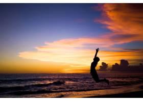 日落时海滩上的人们那个女孩在跳_2440498