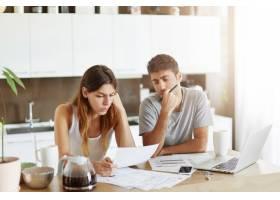 年轻夫妇检查他们的家庭预算_10113386