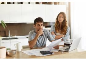 年轻夫妇检查他们的家庭预算_10113441