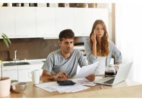 年轻夫妇检查他们的家庭预算_10113443