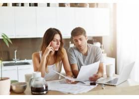 年轻夫妇检查他们的家庭预算_10113743