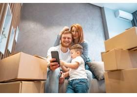 年轻幸福的家庭带着孩子一起坐在沙发上打开_6440950