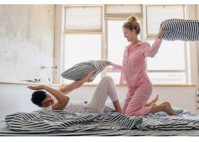 年轻漂亮的夫妇早上在床上玩得很开心独自_9699643