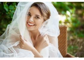 年轻漂亮的金发新娘穿着婚纱戴着面纱微笑_7599913
