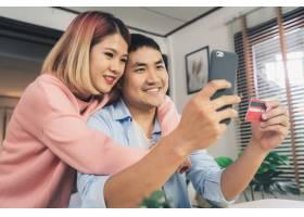 年轻的亚洲家庭夫妇用智能手机讨论新闻_3441200