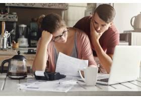 年轻的有压力的高加索夫妇面对财务困难坐_9532838