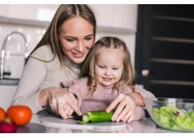 年轻的母亲和女儿在厨房里准备午餐一起享_8471545