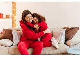 年轻的母亲和青春期的女孩坐在沙发上身穿_12431646