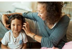 年轻的混血妈妈用无线耳机照看她可爱的三岁_11554351