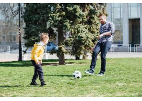 年轻的父亲和他的儿子在公园踢足球_7927332