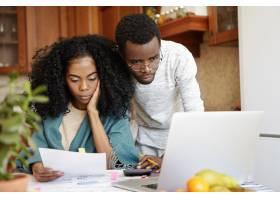 年轻的非洲家庭使用笔记本电脑在线支付水电_9534718