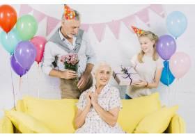 幸福的女人坐在沙发上丈夫和孙女手里拿着_3492417