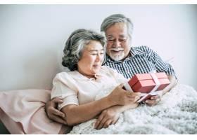 年长的丈夫微笑着在卧室里惊喜地给妻子送礼_4107922
