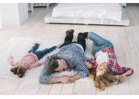 幸福的一家人躺在家里的毛皮地毯上_3831205
