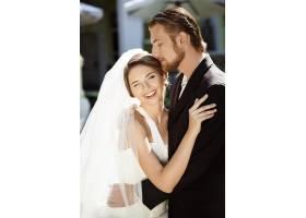 幸福美丽的新婚夫妇在外面微笑拥抱接吻_7599805