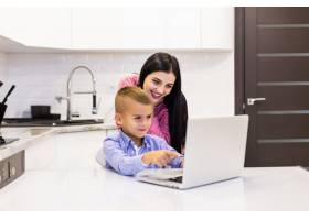 当她的儿子在厨房里使用笔记本电脑学习时_8472471