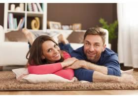 微笑的夫妇在家里的地毯上放松_11100501