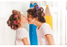 微笑的小女孩和她的母亲在白色上玩耍_10250515