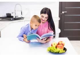 微笑的母亲帮助儿子做作业在厨房里玩得很_8472487