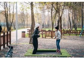 妈妈和女儿一起在秋季公园的蹦床上跳_7560346